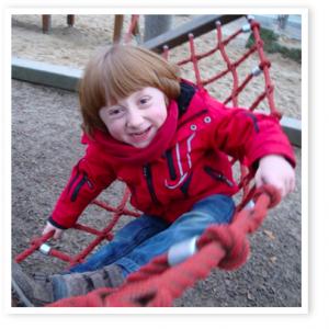 Kind mit OI sitzt lachend auf einen Netzklettergerüst